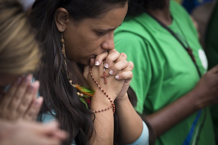 Pilgrim prays during World Youth Day closing Mass in Rio de Janeiro